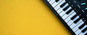 close up stop view of electric keyboard music equipment on yellow background with copyspace for ad your text and content for design concept
