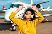 Young pretty girl dancing to the beats of her favorite tracks with her hands up while listening to music over the headphones next to a private airplane parked on an airport runway