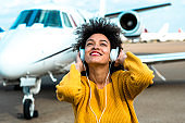 Young girl joyfully listening to music over the headphones in front of a private airplane parked on an airport runway