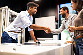 Store seller and a customer shaking hands after agreeing on a purchase in a shop
