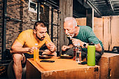 Active elderly man eating a healthy, protein-rich, chicken salad meal together with his personal trainer in a gym gym