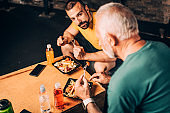 Active senior man and his personal training instructor eating a healthy protein salad meal after training in a gym gym