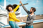 Young, fashionable young couple holding hands and dancing together next private jet parked on an airport tarmac