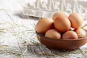 Raw organic brown chicken eggs in clay bowl on white kitchen wooden table