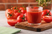 Tasty Tomato juice in a glass with ripe red tomatoes.