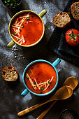 Red vegetarian tomato soup on a dark background, top view. Healthy eating concept