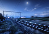 Railroad and blue sky with moon and clouds at night with motion blur effect. Industrial landscape with railway station and blurred background at twilight. Railway platform in move. Transportation