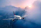 Passenger airplane is flying over clouds at sunset. Landscape with white airplane, low clouds, sea coast, purple sky at dusk. Aircraft is landing. Business trip. Commercial plane. Travel. Aerial view