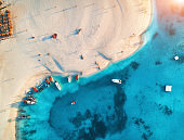 Aerial view of the fishing boats and yachts on tropical sea coast with sandy beach at sunset. Indian Ocean, Zanzibar, Africa. Colorful landscape with boat, transparent blue water. Top view. Travel