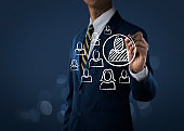 HR, human resources management, recruitment, employment or finding leader concept. Businessman is drawing circle around an officer icon on dark tone background.