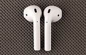 Apple Airpods on a gray surface.