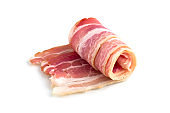 Slices of bacon on a white background. Raw rolled bacon on a white background.