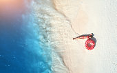 Aerial view of the beautiful young lying woman with pink donut swim ring on the white sandy beach near blue sea with waves at sunset. Summer holiday. Top view of slim girl, clear water. Indian Ocean