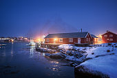 Beautiful norwegian Rorbu on sea cost and snowy mountain at night in winter. Lofoten islands, Norway. Landscape with red houses, fishing boats, snow covered rocks  in fog, reflection in water at dusk