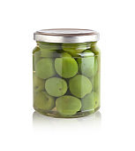Marinated olives in a glass jar. Green olives in a jar closeup on a white background. Jar Isolated on a white background.
