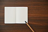 A horizontal photograph of a pen and an off white plain page of a notepad placed aesthetically over a wooden dark brown color horizontal background.