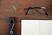 A horizontal photograph of stationery, like diary, a notepad, clips, spectacles placed aesthetically over a wooden dark brown color horizontal background.