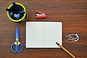 A horizontal photograph of stationery, like pen, diary, scissors, stapler, tags placed aesthetically over a wooden dark brown color horizontal background.