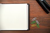 A horizontal photograph of an off white plain page of a notepad along with a black color peg or clothespin, partially visible and colourful paper clips placed aesthetically over a wooden dark brown color horizontal background.
