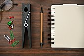 A horizontal photograph of stationery, like pen, diary, spiral notepad, clips, pins, spectacles placed aesthetically over a wooden dark brown color horizontal background.