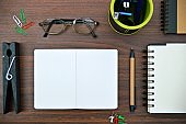 A horizontal photograph of stationery, like pen, diary, spiral notepads, colored thumbpins,  pen stand with pens, stapler, spectacles placed aesthetically over a wooden dark brown color horizontal background.