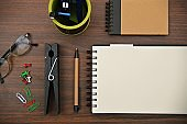 A horizontal photograph of stationery, like pen, diaries, pen stand with pens, stapler, a big clip, paper clips and pins placed aesthetically over a wooden dark brown color horizontal background.