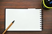 A horizontal photograph of a pen placed slanting over white plain page of a spiral notepad placed aesthetically over a wooden dark brown color horizontal background.