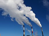 White harmful smog in blue sky vaporing from industrial pipes