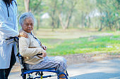 Doctor help and care Asian senior or elderly old lady woman patient sitting on wheelchair at nursing hospital ward : healthy strong medical concept