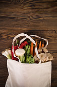 Fresh vegetables in bio eco cotton bags on old wooden table.