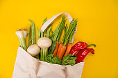 Fresh vegetables in bio eco cotton bags on yellow background. Zero waste shopping concept.