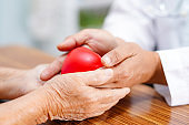 Doctor give red heart to Asian senior or elderly old lady woman patient  : healthy strong medical concept