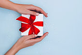 Woman's hands with manicure hold gift box with red ribbon on pale blue background with glitters. Festive concept.
