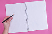 human hand holds black wooden pencil over empty open notebook