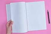 empty open notebook in a cell and a female hand