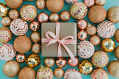 Gift box wrapped in craft paper with pink ribbon and golden Christmas tree balls on pale blue background with glitters.