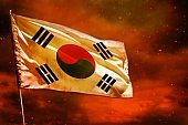 Fluttering Republic of Korea (South Korea) flag on crimson red sky with smoke pillars background. Troubles concept.
