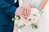 Hands of bride and groom with wedding rings on beautiful bouquet of roses.