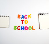 inscription back to school from multi-colored plastic letters and a stack of notebooks with blank white sheets
