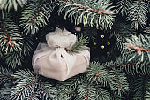 Christmas present wrapped with white furoshiki fabric on fir branches. Eco friendly gift.