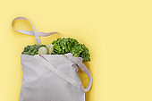 Reusable bag with green salad, broccoli and zucchini on yellow background. Zero waste and plastic free shopping concept.