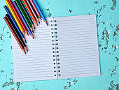 open notebook in a line and multi-colored wooden pencils