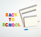 inscription back to school from multi-colored plastic letters and a stack of notebooks