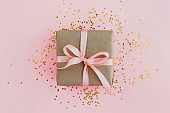 Gift box wrapped in craft paper with pink ribbon on pale pink background with glitters. Festive concept.