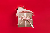 Female hand holding gift box wrapped in craft paper with pink ribbon through a hole in red background.