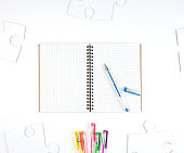 open notebook in a cell and a blue pen on a white background