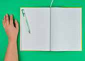 open checked notebook and female hand