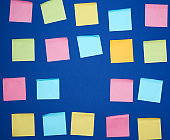 many glued square multi-colored blank stickers on a blue background
