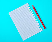 empty rectangular white sheet torn out of notepad and wooden red pencil