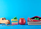 ripe red apple,  stack of notebooks and multi-colored wooden pencils